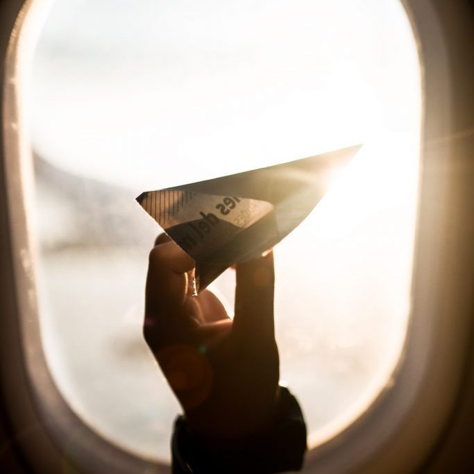 Paper airplane in airplane window